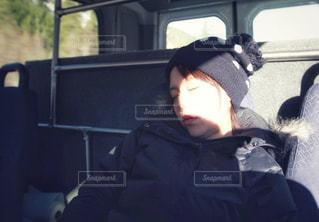 車の中で座って寝るニット帽を被った女性の写真・画像素材[2722606]