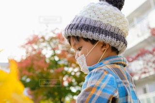 マスクと帽子をした男の子の横顔の写真・画像素材[2722612]