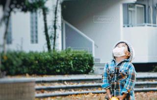 公園でマスクをして見上げる男の子の写真・画像素材[2723312]