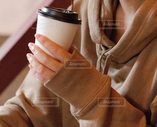ドリンクを持っているパーカーを着た女性の手の写真・画像素材[2726640]