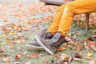 公園のベンチに座っているブーツの女性と公園の紅葉の写真・画像素材[2729247]