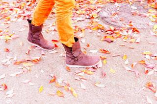 紅葉した落ち葉の公園を歩くブーツの女性の足元の写真・画像素材[2735961]
