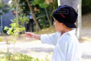 公園で手を伸ばしている帽子をかぶった男の子の横顔の写真・画像素材[2753931]