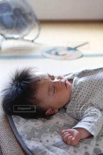 畳の部屋で寝る赤ちゃんとうちわと扇風機の写真・画像素材[3635764]