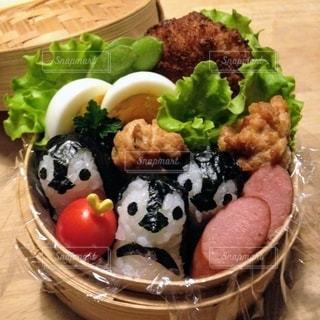 机の上のペンギンおにぎりとソーセージと唐揚げのお弁当の写真・画像素材[3643210]