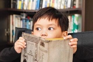 たくさんの本の本棚の前で座って本を読む男の子の写真・画像素材[3753691]