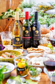食べ物の皿が付いたテーブルの上にワインのボトルの写真・画像素材[4348614]
