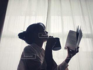 窓辺でカップを持ちながら本を読む女性の横顔の写真・画像素材[4436110]