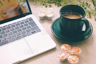 一杯のコーヒーとテーブルの上に座っているラップトップ コンピューターの写真・画像素材[1265518]