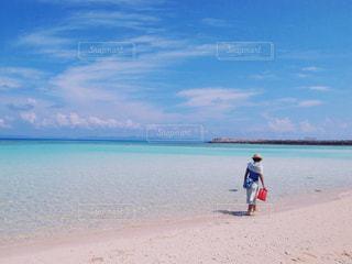 水の体の近くのビーチに立っている人の写真・画像素材[1315788]