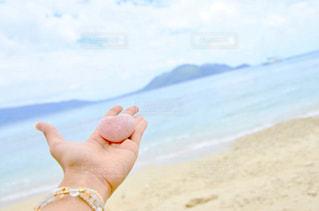 ビーチで水のボトルを持っている手の写真・画像素材[1317605]