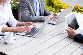 ラップトップを使ってテーブルに座っている人々のグループの写真・画像素材[2444716]