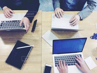 ラップトップコンピュータを使ってテーブルに座っている人々のグループの写真・画像素材[2446153]