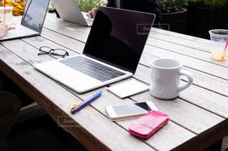 木製のテーブルの上に座っているラップトップコンピュータの写真・画像素材[2449029]