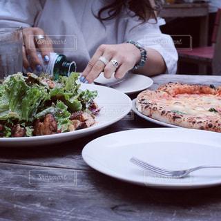 食品のプレートをテーブルに座っている女性 - No.763488