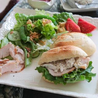 皿の上にサンドイッチとサラダの写真・画像素材[3204515]