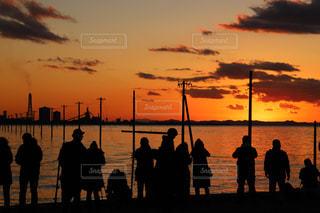水の体の横に立っている人のグループの写真・画像素材[955657]
