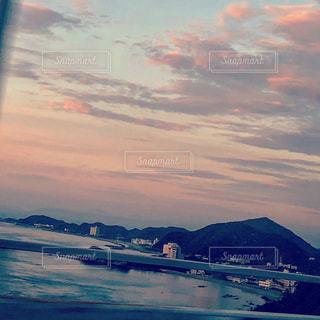 背景の山が付いている水の体に沈む夕日の写真・画像素材[1280125]