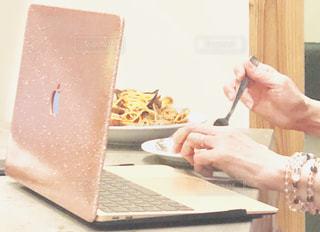 ノートパソコンを使ってテーブルに座っている人の写真・画像素材[2311294]