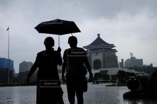 傘を保持している水の体の横に立っている人 - No.813527