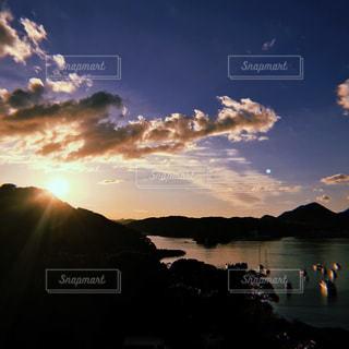 背景の山が付いている水の体に沈む夕日の写真・画像素材[1270411]