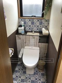 ウィンドウの横に座っている白いトイレつきバスルームの写真・画像素材[802493]