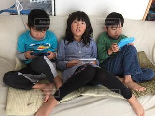 ソファーに座ってゲームをしている兄弟の写真・画像素材[834565]