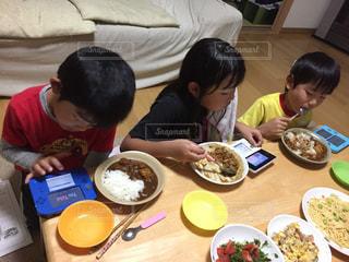 食品のプレートをテーブルに座っている人々 のグループの写真・画像素材[843759]