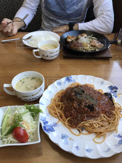 食べ物の皿を持ってテーブルに座っている人の写真・画像素材[2768069]