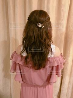 カーテンの前で髪をかきあげる少女の写真・画像素材[1647547]