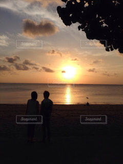 ビーチでの背景の夕日に人々 のグループの写真・画像素材[1847969]