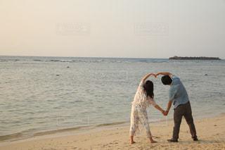 浜辺の砂の上にフリスビーを持っている男の写真・画像素材[2170275]