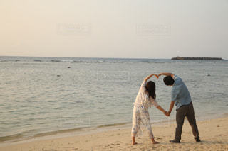 浜辺の砂の中でフリスビーを持っている男の写真・画像素材[2263288]