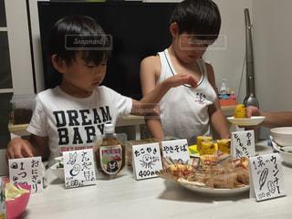 食物と一緒にテーブルに座って若い男の子 - No.784692