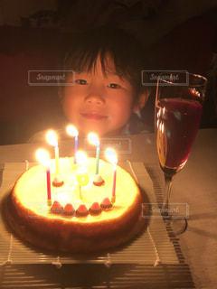 キャンドルとバースデー ケーキでテーブルに座っている小さな男の子の写真・画像素材[1670215]