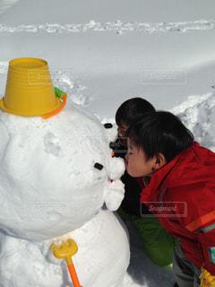 雪の中で立っている少年の写真・画像素材[1673593]