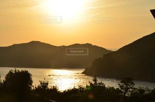 山を背景にした水の体に沈む夕日の写真・画像素材[3396325]