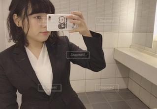 カメラにポーズ鏡の前に立っている女性の写真・画像素材[956642]