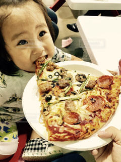 皿の上のピザのスライスを食べる女 - No.765241