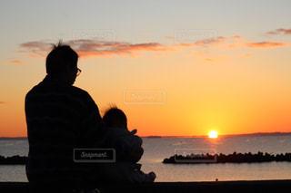 浜辺から日の出を拝む親子の写真・画像素材[2857680]