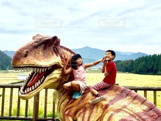 恐竜の前のベンチに座っている人の写真・画像素材[824858]