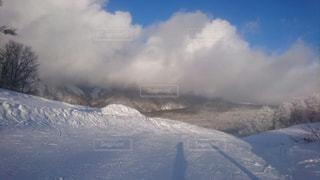 雪に覆われた斜面をスキーに乗る男の写真・画像素材[958351]