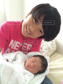 ベッドの上で赤ちゃんを保持している女性 - No.895376