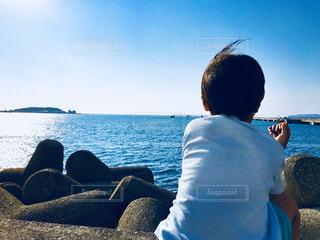 水の体の横に座っている男 - No.1098247