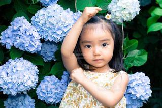 花の前に立っている女の子の写真・画像素材[1884724]