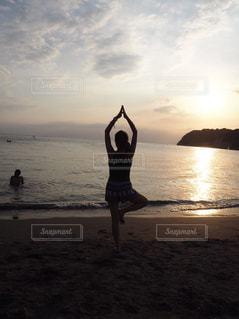 水の体の近くのビーチに立っている人の写真・画像素材[1000667]