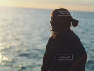 水の体の横に立っている人の写真・画像素材[1043972]