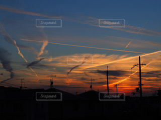 夕焼けとヒコーキ雲の写真・画像素材[1268946]