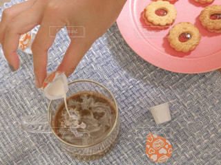 テーブルに食べ物のプレートを持っている人の写真・画像素材[1268586]