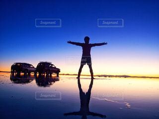 水の体の横に立っている人の写真・画像素材[928050]
